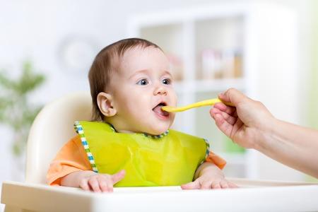 bebês: mãe alimentando o bebé na cozinha de casa
