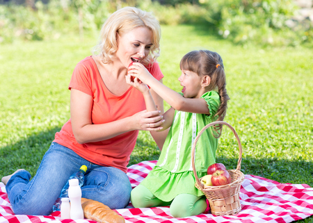 comiendo pan: Happy family at summer vacation concept. Mother and daughter kid having picnic playing in park outdoors.