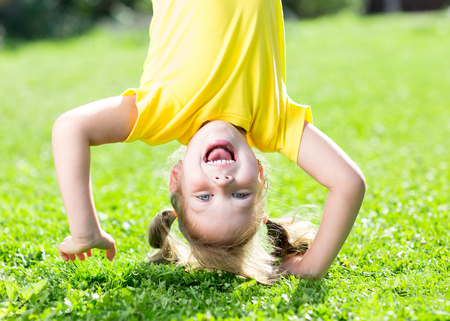 sun down: happy child girl standing upside down on her head on grass in summer Stock Photo