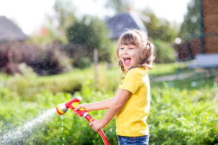 pours: Happy child girl pours water from a hose in garden Stock Photo