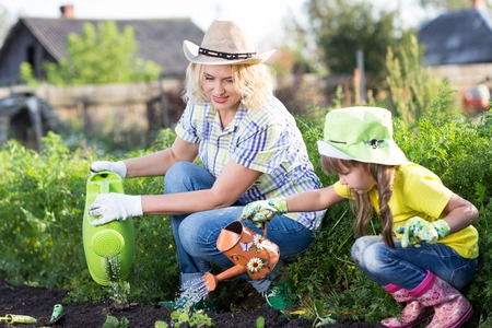 wateringcan: Mother and child daughter working in the garden