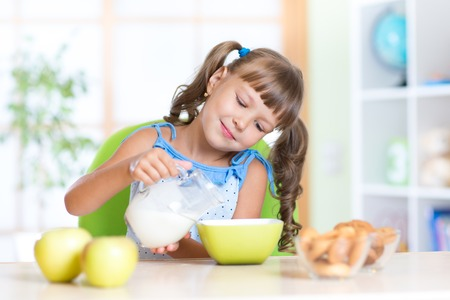 children eating: Child little girl having breakfast at nursery