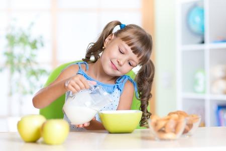 comiendo cereal: Niño niña de desayunar en la guardería