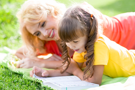 grassplot: mother reading a book to kid outdoors in summertime Stock Photo