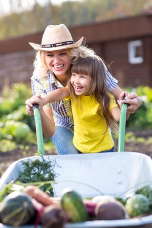niño empujando: Madre e hija Niño empujando la carretilla con la cosecha