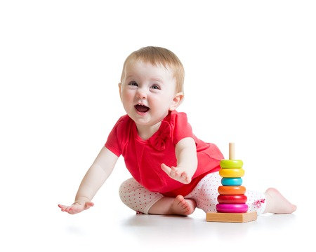 baby sitting: cheerful child little girl playing with colorful toy isolated on white