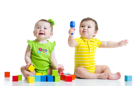 Two adorable babies playing with educational toys. Toddlers girl and boy sitting on floor. Isolated on white background.