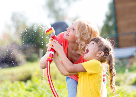 domestic garden: Happy woman and kid daughter watering in domestic garden at summer day Stock Photo