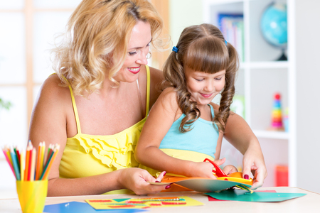 child education: Mother with child girl drawing and cutting together