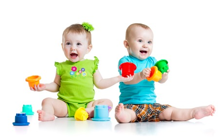Two cute babies playing with color toys. Children girl and boy sitting on floor. Isolated on white background. Stock Photo