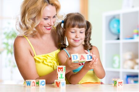 teaches: Mother teaches daughter child letters and words playing with cubes