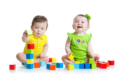 Two adorable babies kids playing with educational toys. Toddlers girl and boy sitting on floor. Isolated on white background.