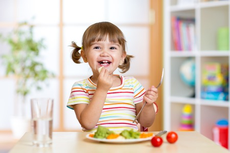 happy kid girl eating healthy food vegetables at home Stock Photo