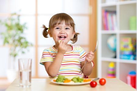 école maternelle: heureux jeune fille mangeant des légumes d'aliments sains à la maison Banque d'images