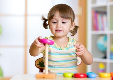 children  play: Child girl playing with toy indoors at home