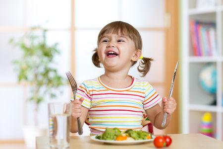 a little dinner: happy little girl with healthy food for dinner at home Stock Photo