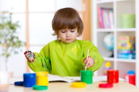 mandil: niña de color Niño con las manos pintadas pinta delantal weared en la guardería