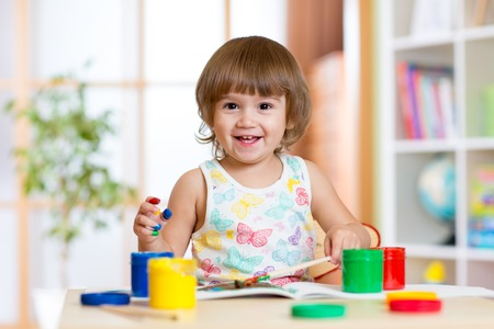 baby playing: Happy child girl with hands painted color paints at home