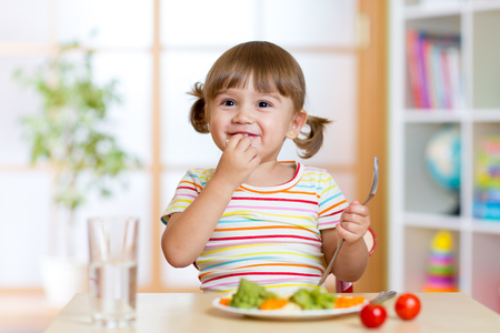 eating: Happy child eats vegetables sitting at table in nursery