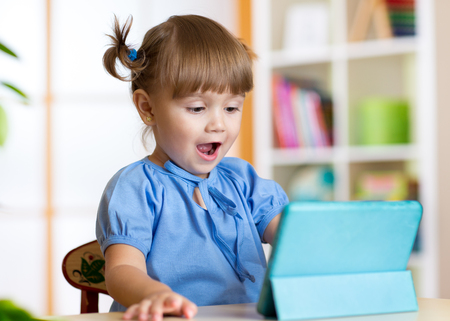 digital tablet: child girl playing with a digital tablet at home