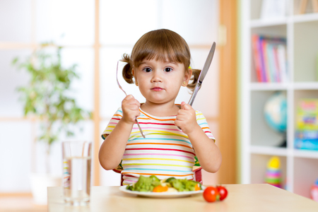 kind meisje met vork en mes klaar om te eten