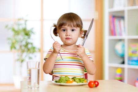 niños comiendo: niña niño con tenedor y cuchillo listo para comer