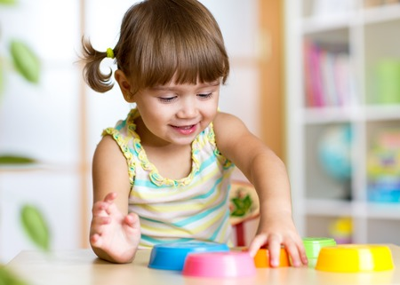 school activities: happy kid little girl playing with toys indoors