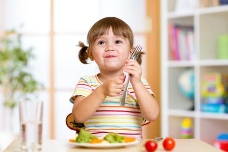 kinder: muchacha ni�o come alimentos vegetales saludables en el hogar o jard�n de infancia Foto de archivo
