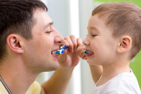 Kindjongen en zijn vader poetsen tanden in de badkamer Stockfoto