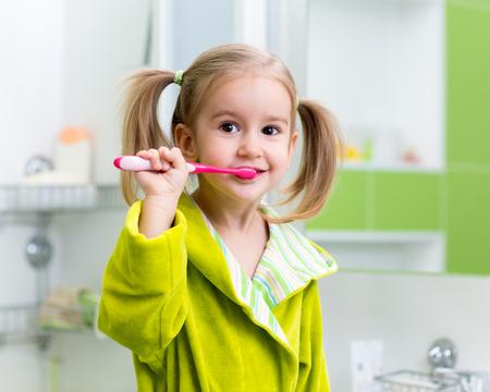 child protection: Kid child little girl brushing teeth in bathroom