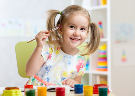 smiling kid girl painting at home or kindergarten Stok Fotoğraf