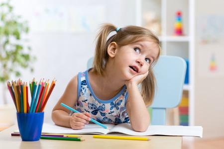 rêveuse jeune fille dessin avec des crayons de couleur Banque d'images