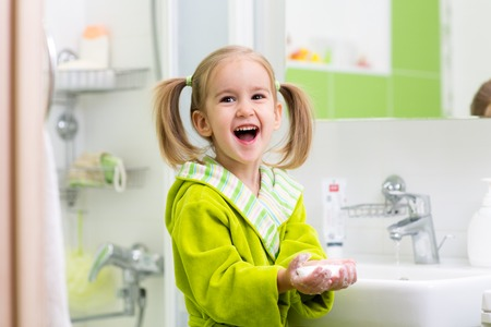 kids hand: Little child girl washing her hands in bathroom. Stock Photo