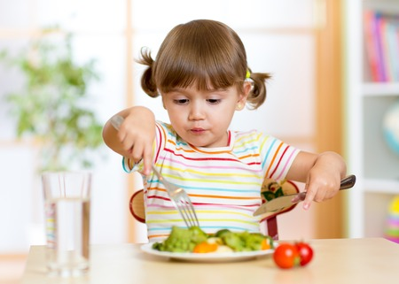 kid girl eating healthy food at home or kindergarten