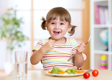 niña comiendo: sonriente niña niño comiendo verduras saludables en la cocina