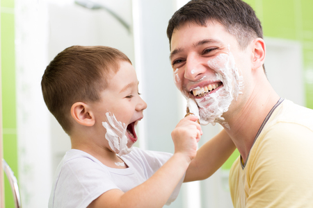 shaving cream: Father and his kid son playing in bathroom. Child boy putting shaving cream on dad face