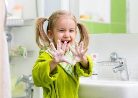 Kind Waschen der Hände und zeigt Seifen Palmen