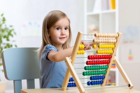 guardera: ni�a ni�o jugando con juguetes en el interior Foto de archivo