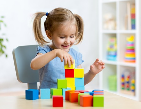kinderen: kind meisje spelen houten speelgoed thuis of kleuterschool