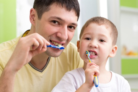 tooth: child boy and his father brushing teeth in bathroom Stock Photo