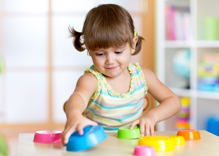 nursery school: happy kid little girl playing with toys indoors