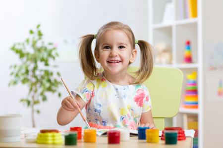 kindergarten: pretty child kid girl painting with watercolours at home