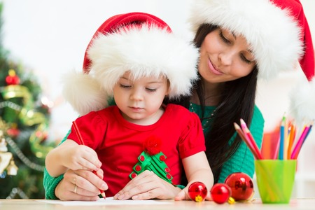 beautiful letters: Child girl and her mother writing letter to Santa Stock Photo