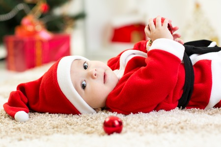 baby near christmas tree: Cute baby boy weared Santa lying near Christmas tree Stock Photo