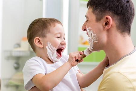应用在他的父亲面孔的快乐的儿童小男孩剃须膏在卫生间里