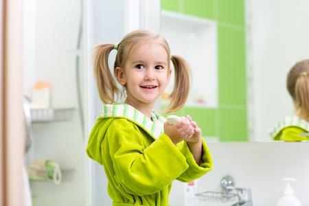 Cute child kif little girl washing hands in bathroom