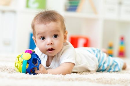 Joyful baby kid lying on the carpet with toy in nursery room Stock Photo - 46805659