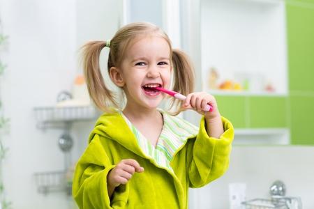 Smiling child kid girl brushing teeth in bathroom Standard-Bild