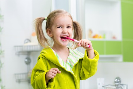 tooth paste: Smiling child kid girl brushing teeth in bathroom Stock Photo