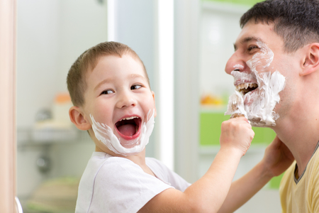 playful father and his kid son shaving and having fun in bathroom